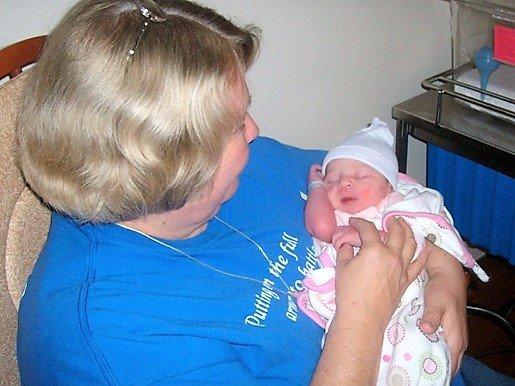 grandma holding newborn baby girl